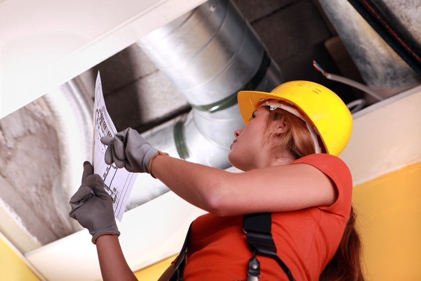 Female-HVAC-technician-going-through-the-the-air-duct-diagram-for-air-duct-repair-and-maintenance