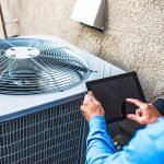 HVAC System Maintenance Man running an app tocheck a condenser unit