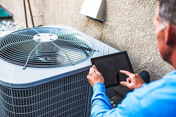 HVAC System Maintenance Man running an app tocheck a condenser unit