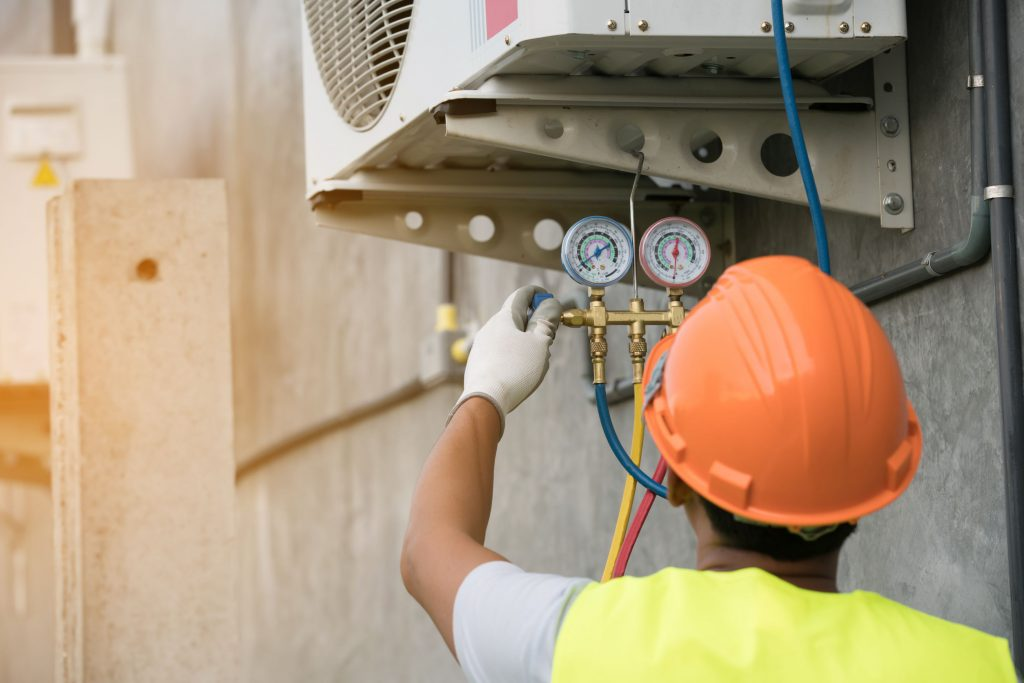 hvac-technician-runs-the-air-conditioning-refrigerant-from-the-tank-1024x683