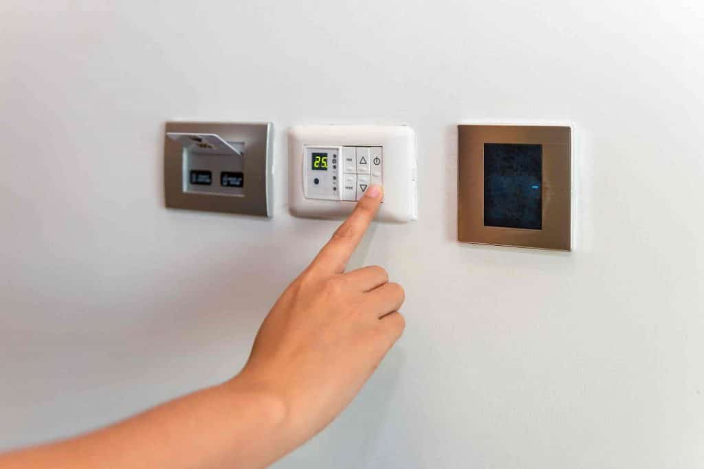 lady-adjusting-the-central-heating-control-panel-termostat-before-going-to-bed-1024x683