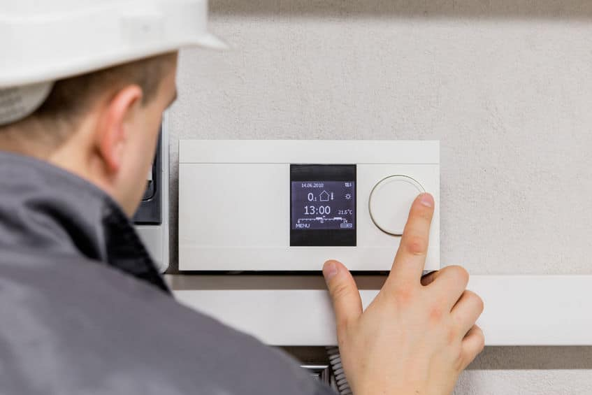 technician-adjusting-a-Programmable-HVAC-Thermostat-to-save-energy